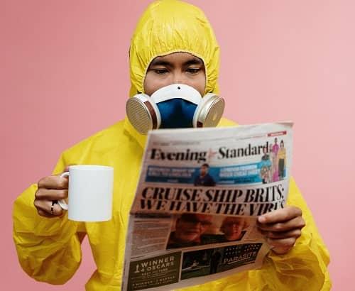 Ein Mann in gelben Schutzanzug, trinkt Kaffee und liest eine Zeitung