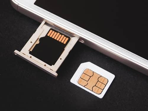Eine Sim Karte liegt neben einem Handy