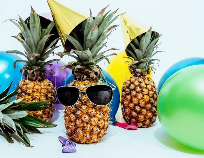 Eine Ananas mit Faschingshütchen, Luftballons und einer Sonnenbrille