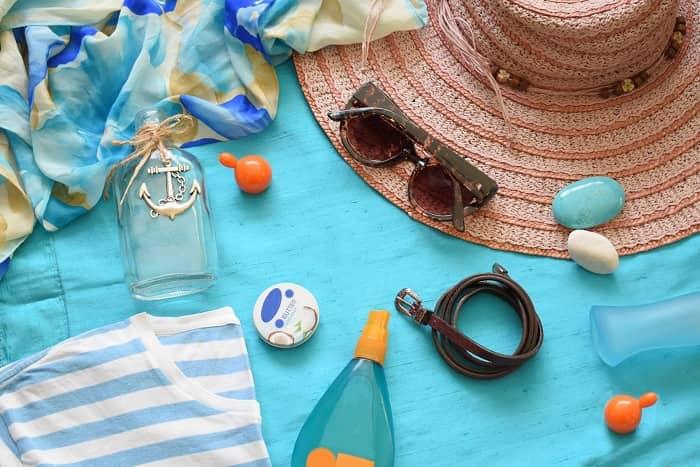Eine Türkisfarbene Stranddecke mit einer Sonnenbrille, Sonnenmilch und etlichen anderen Utensilien