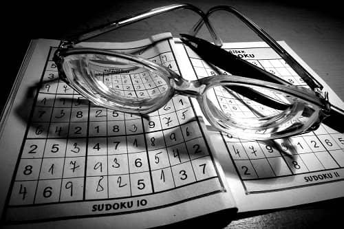 Ein Sudoku Heft liegt auf dem Tisch, darauf eine Brille und ein Kugelschreiber