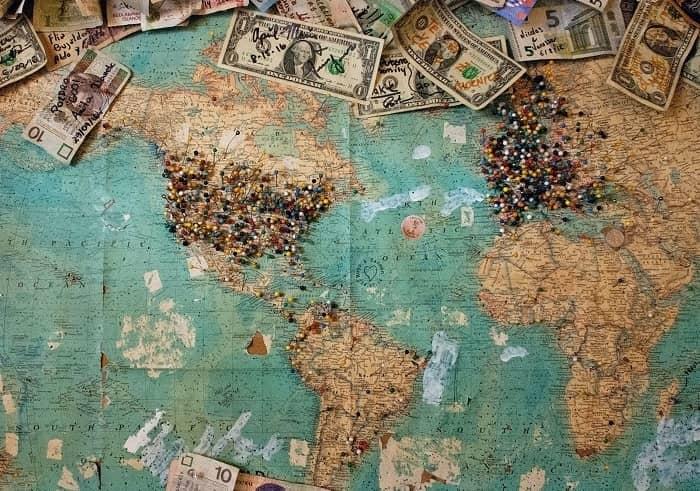 Auf einer Weltkarte sind viele Orte angepinnt und es liegen beschriftete Geldscheine, zu den jeweiligen Ländern mit Notizen, darauf