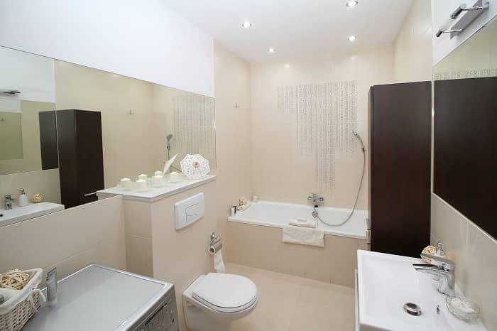 Ein schönes in beige gehaltenes Bad mit Badewanne und großem Spiegel