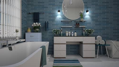 Ein Bad, mit Badewanne und großzügigem Waschtisch und Fliesen in verschiedenen Blautönen