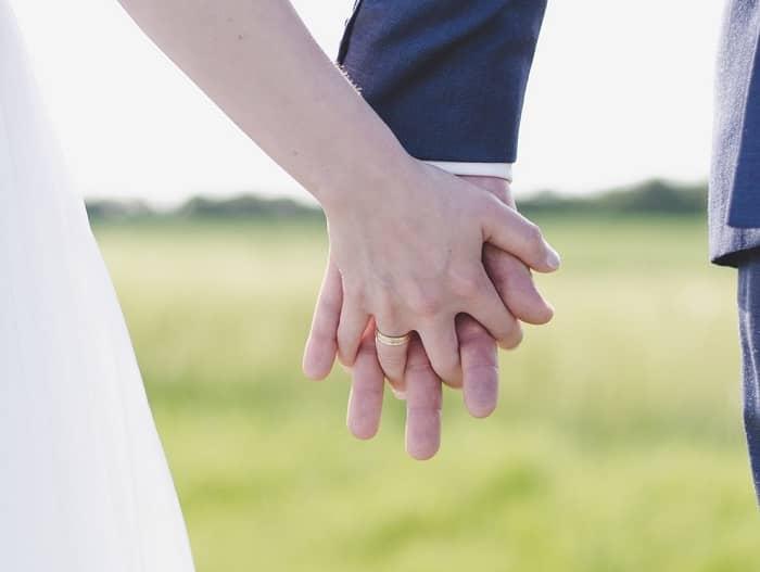 Ein Pärchen hält sich die Hände, man sieht die beiden Eheringe
