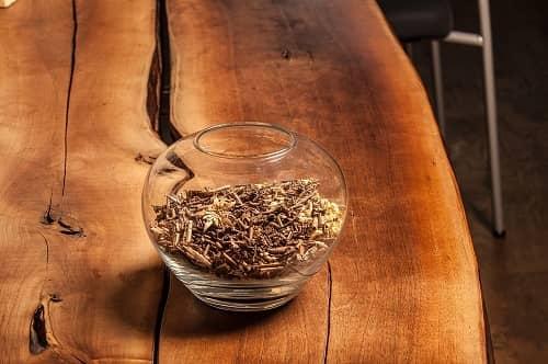 Ein Holztisch auf dem eine Glasschale mit Holzspänen steht