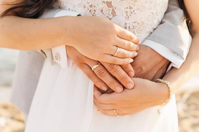 Mann hält seine Frau von hinten, die Hände liegen übereinander und man sieht die Eheringe
