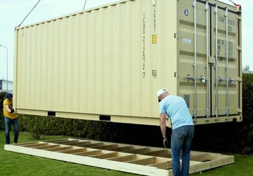 Ein großer Container wird gerade auf ein Schraubfundament aus Holz aufgestellt
