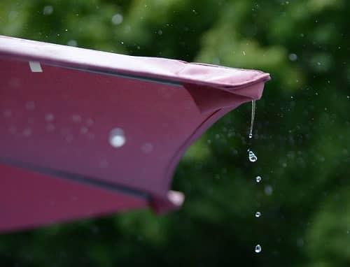 Ein Sonnenschrirm steht im Regen