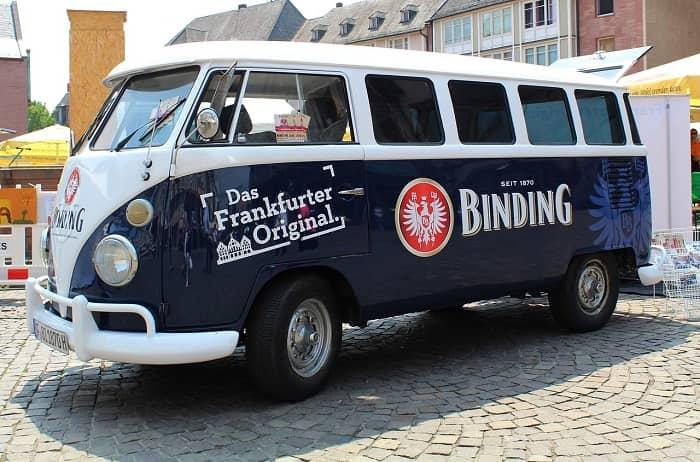 Ein dunkelblau/weißer VW-Bus mit großer Binding Bier Werbung
