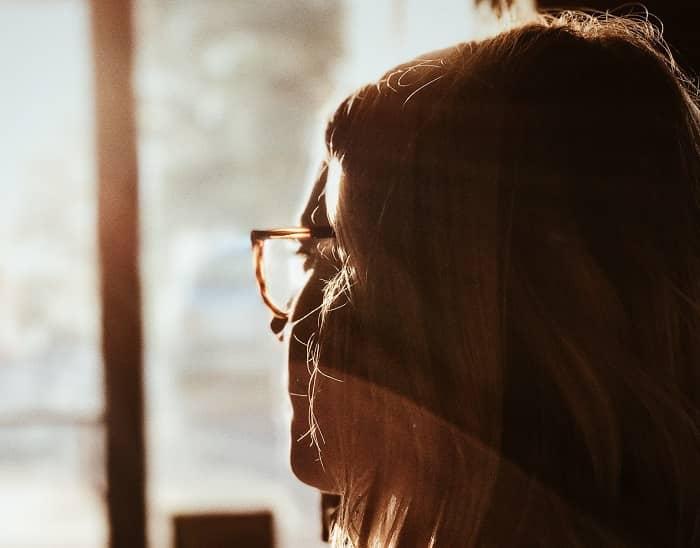 Eine junge Frau sieht sorgenvoll aus einem Fenster