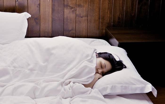 Eine junge Frau liegt schlafend im Bett mit weißer Bettwäsche