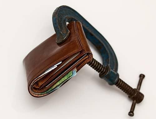Ein Geldbeutel wird von einer Schraubzwinge zusammengedrückt