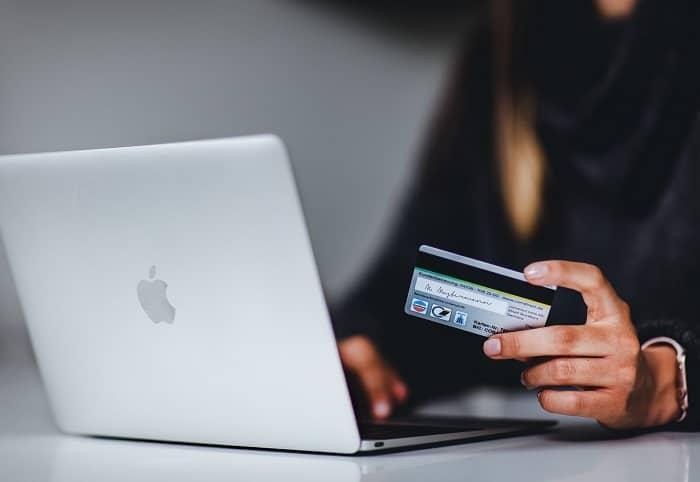 Frau sitzt vor einem Laptop und hält eine Kreditkarte in der Hand