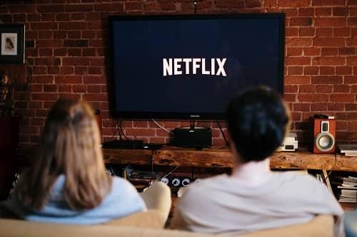 Ein junges Paar sitzt vor einem Flachbildschirm, mit vielen Lautsprechern drumherum