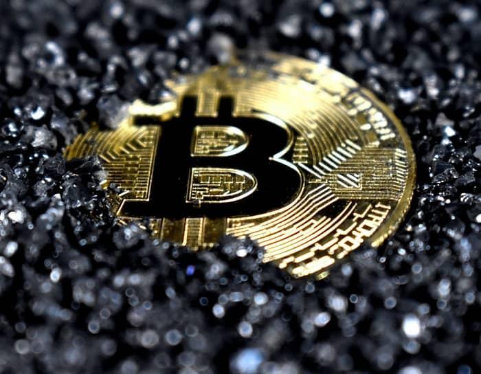 Eine Bitcoin Münze liegt in schwarzen Deco Steinen