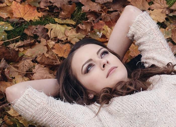 Eine junge, perfekt geschminkte Frau liegt im Herbstlaub