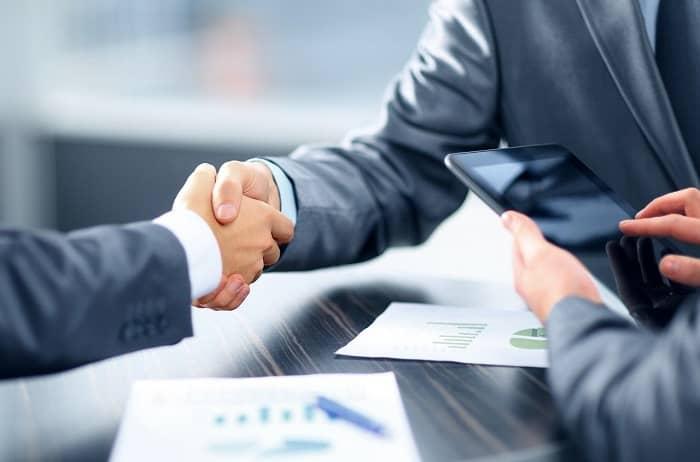 Zwei Männer geben sich die Hände um einen Vertragsabschluß zu besiegeln