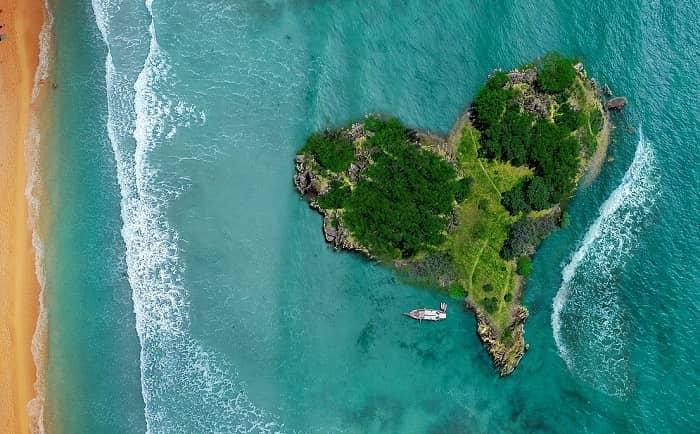 Eine kleine herzförmige und grüne Insel liegt einem Strand vorgelagert