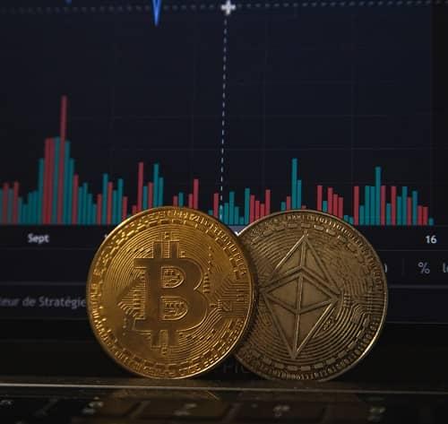 Zwei Bitcoin Münzen liegen auf einem Laptop der einen Kursverlauf anzeigt