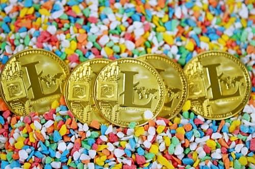 Fünf Litecoin Münzen liegen präsentiert auf bunten Dekosteinen