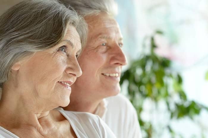 Ein Seniorenpaar sitzt eng beieinander und schaut auf den selben Punkt